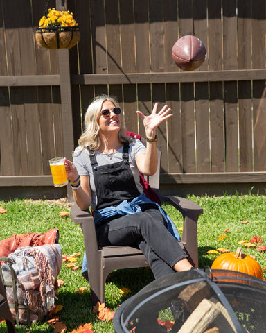 Blonde woman sitting in chair holding glittery beer with Sugar Mama Shimmer Harlow Gold edible glitter for drinks about to catch a football.