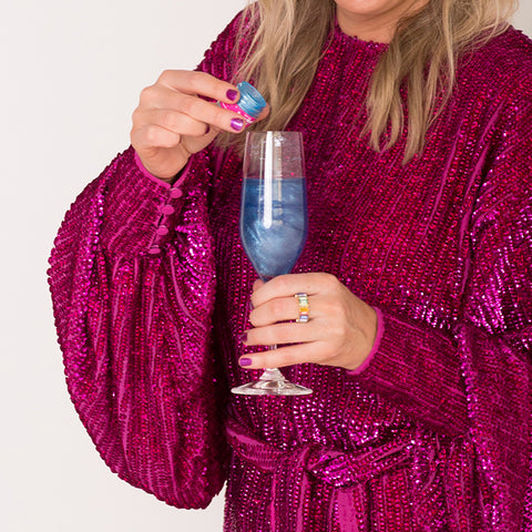 Woman in magenta sequin dress holding champagne glass and blue edible glitter for drinks by Sugar Mama Shimmer. Her champagne has Electric Beach Blue edible glitter for drinks in it.