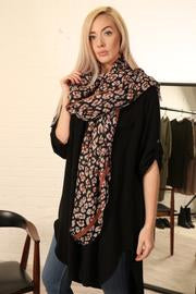 A Black Leopard Print Scarf With Tan Contrasting Border.