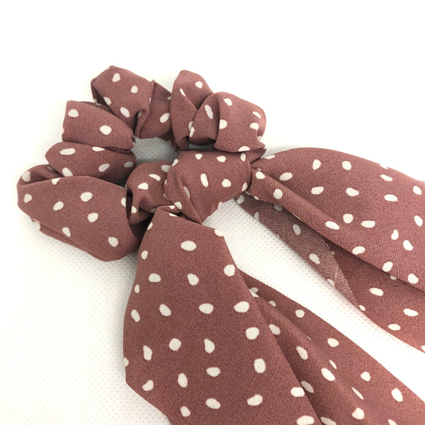 Switch up your ponytail look with this hair scrunchie scarf which features a dusty pink polka dot pattern to complete any hair look.
