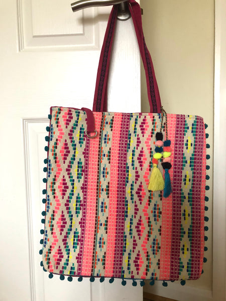 This bright tote, is lovely and big (but can be cinched in at the sides with closure straps to make it more compact when you have less to carry).  Bright woven fabric on both sides, edged in bright pink, trimmed with blue pompoms.   A small inside pocket in the pink lining, magnetic clasp closure and a perfectly contrasting pom-pom tassels.  With the side-cinching clasp undone, this measures 57cms wide and 40cms deep, with a handle drop of 28cms