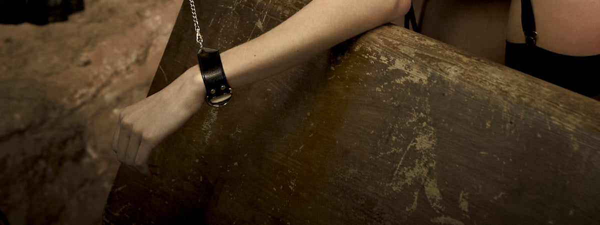 Leather handcuffs with gold chain
