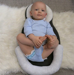 Baby in lounger bed with adjustable leg pillows