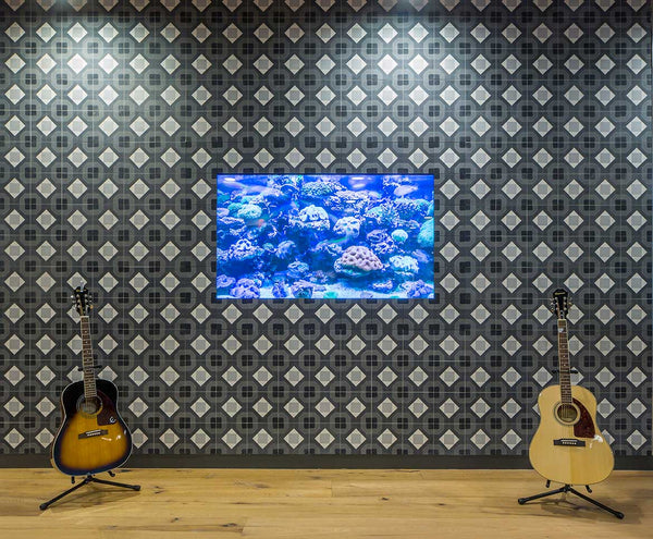 Two guitars infront of black and white patterned tiles