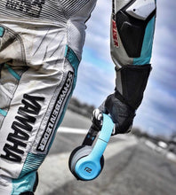 Motorcycle racer holding blue Rival Headphones