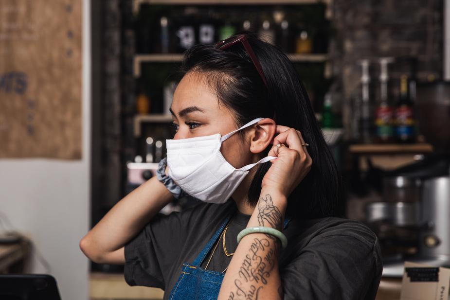 Store Owner putting on her face mask