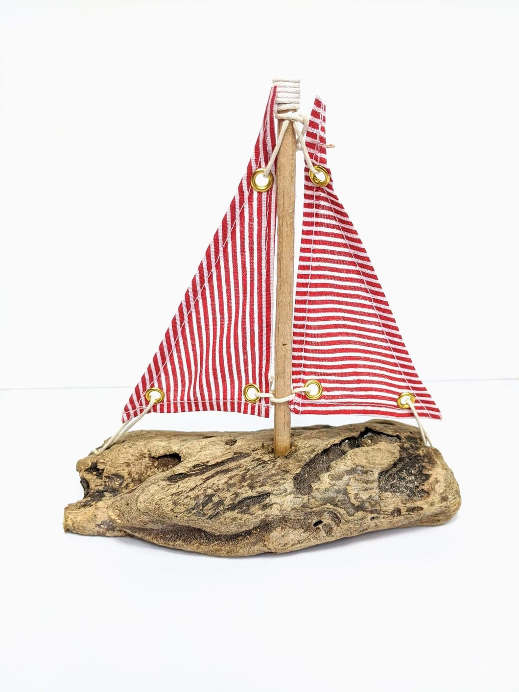 Driftwood Boat with Red and White Striped Sails