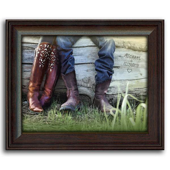 This western style art is a closeup of two people wearing cowboy boots resting on a fallen tree -framed under glass
