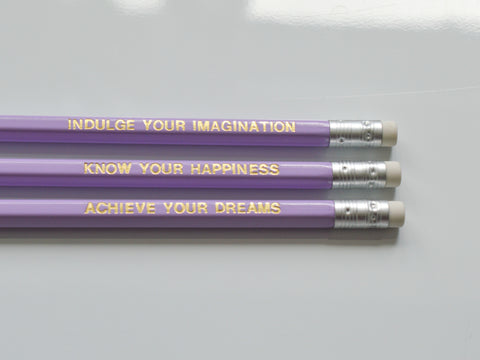 Gold Foiled lilac imagination pencils reading: indulge your imagination, know your happiness, achieve your dreams