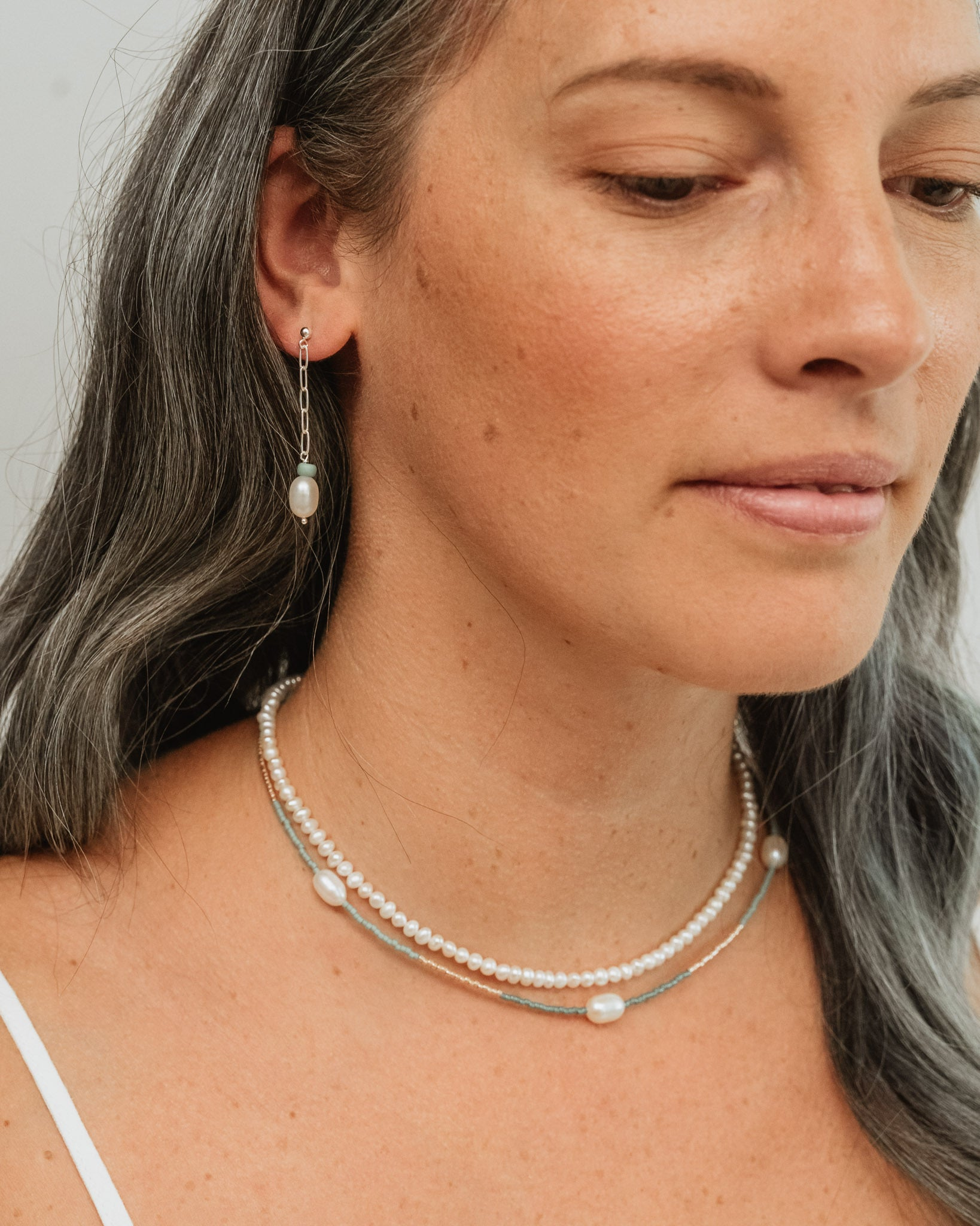 woman wearing pearl string necklace and beaded pearl necklace