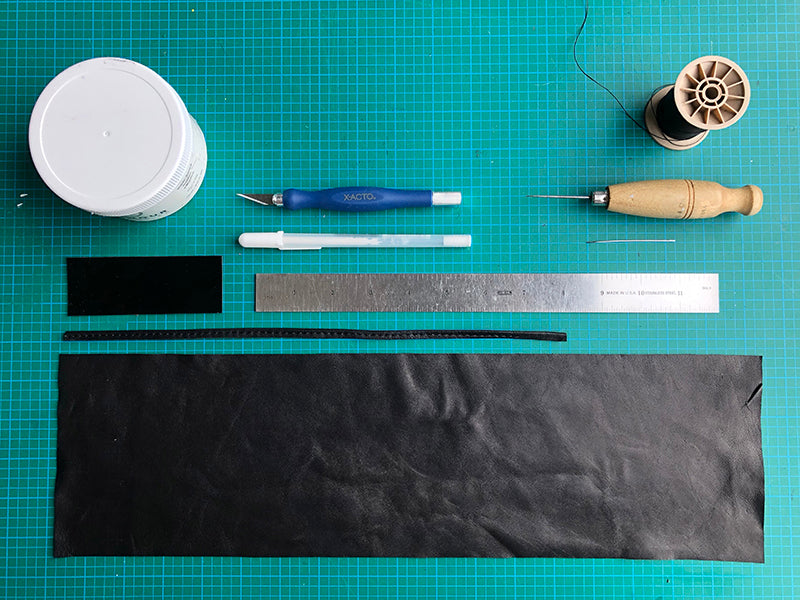 Photo of leather pieces, ruler, pen, knife on cutting mat
