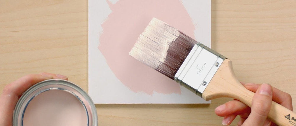 top down view of pink paint bucket and hand holding brush with pink paint over white square block with pink painted circle