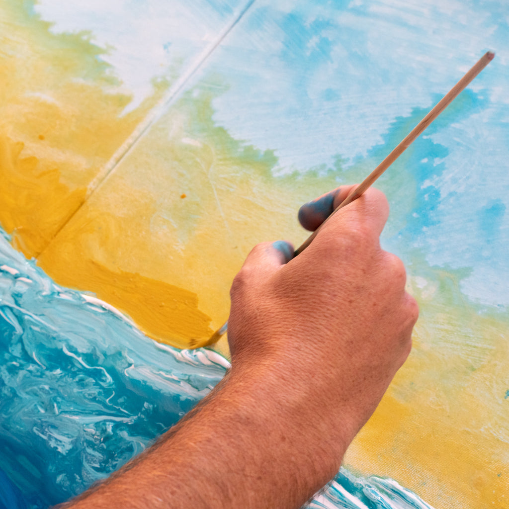Zach Crawford painting an abstract ocean painting