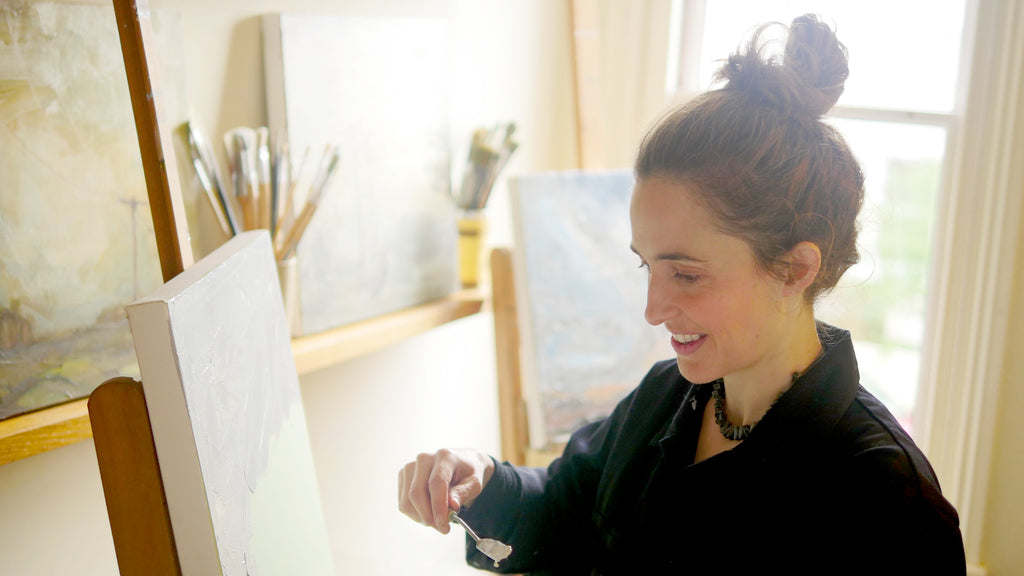 Grace Wilmshurst, artist, in her studio painting canvases.