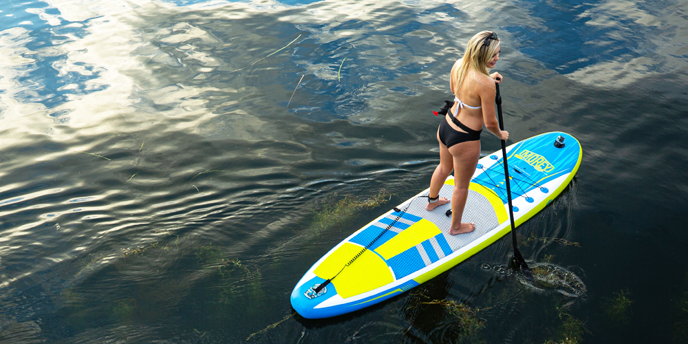 Girl paddling on a TRAVLR SUP, back side view