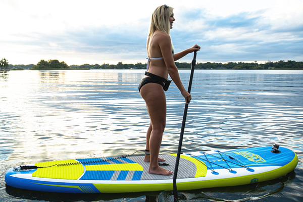 Girl paddling on a TRAVLR SUP, lateral side view