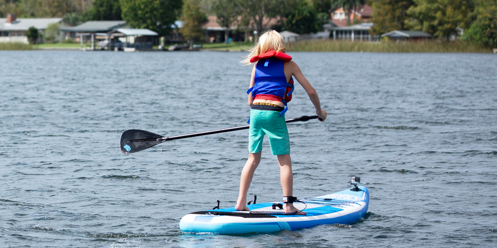 Boy paddling on a X-PLORE SUP, back side view
