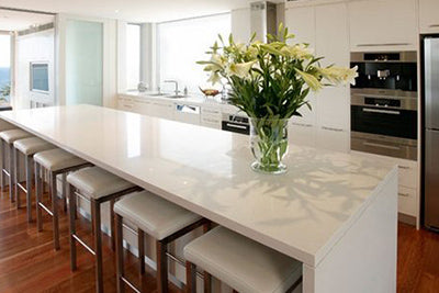 modern kitchen with long white island and stools