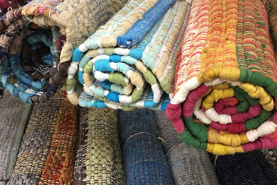 3 rolled up rugs in various colours