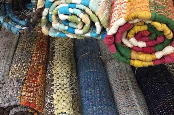 stacks of rolled up rugs in various colours