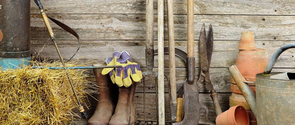 wooden wall with boots, pots, hay, and various tools leaning against it