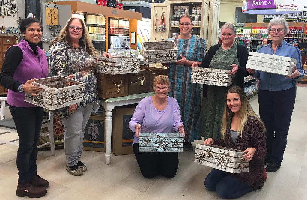 7 women holding decorated apple crates