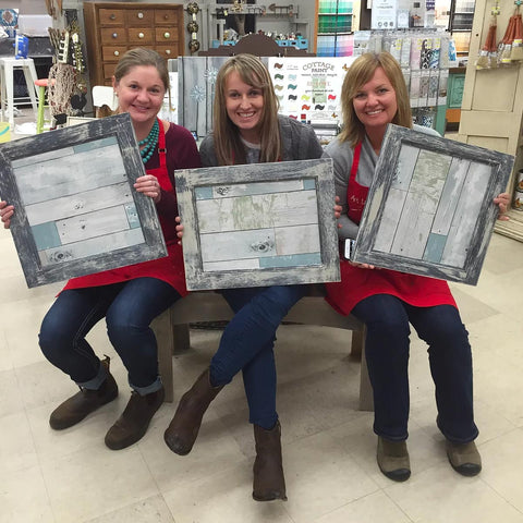 3 women in red aprons holding up decorated picture frames