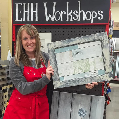woman with red apron holding up decorated picture frame