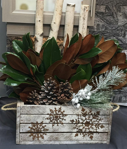 decorated apple crate with snowflakes and various botanical items inside