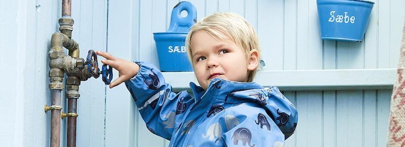 Boy in navy elephant rain set