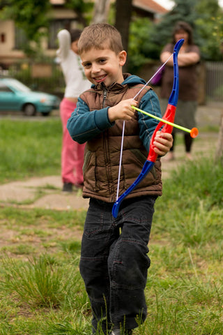 Kid playing with bow and arrow