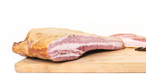 The cross section of a bacon slab on a cutting board to show the fat to meat ratio.
