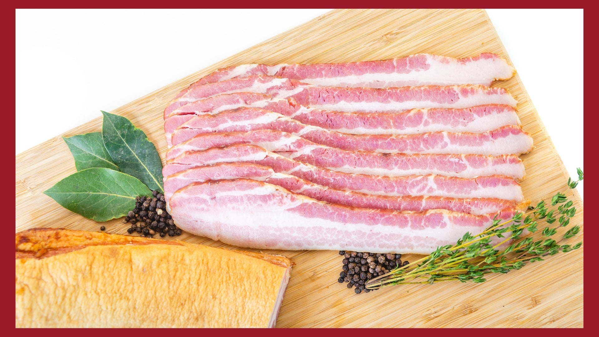 Eight bacon strips on a cutting board with peppercorns and herbs around them.