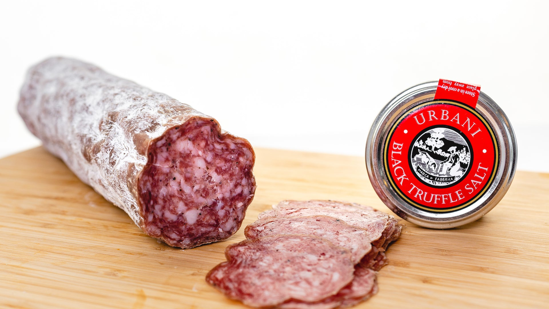 Black truffle salami on a cutting board with the cut end facing the camera and several slices of salami in the foreground.