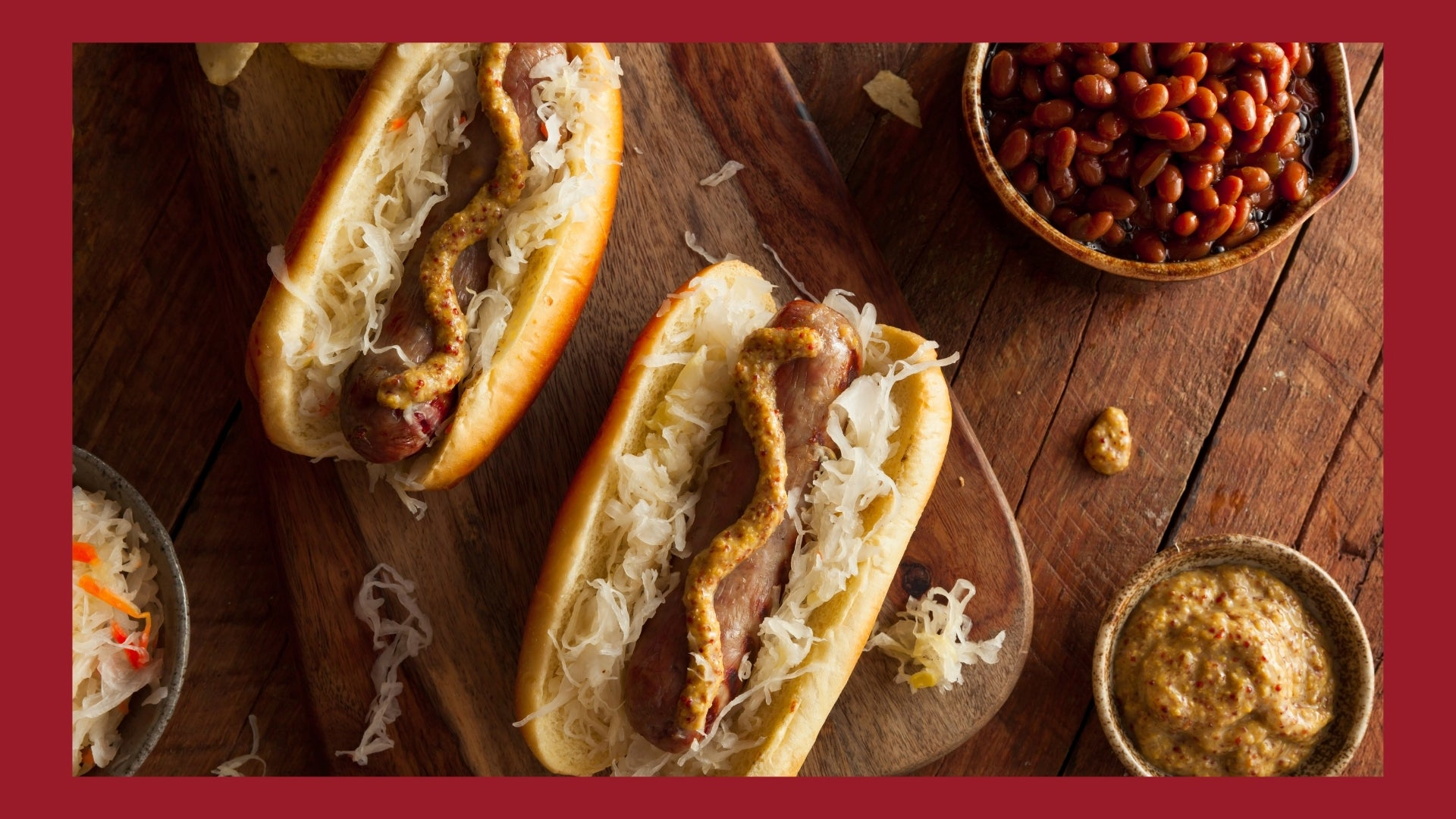 Bratwursts in buns and topped with sauerkraut, onions, and brown mustard on a wooden cutting board.