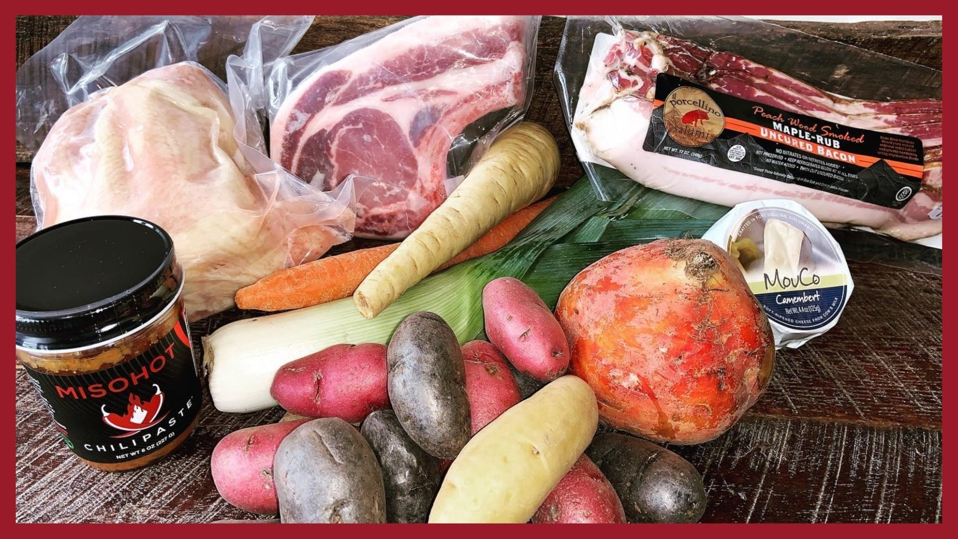 A picture of vegetables, meat, cheese and canned goods on a wood table.