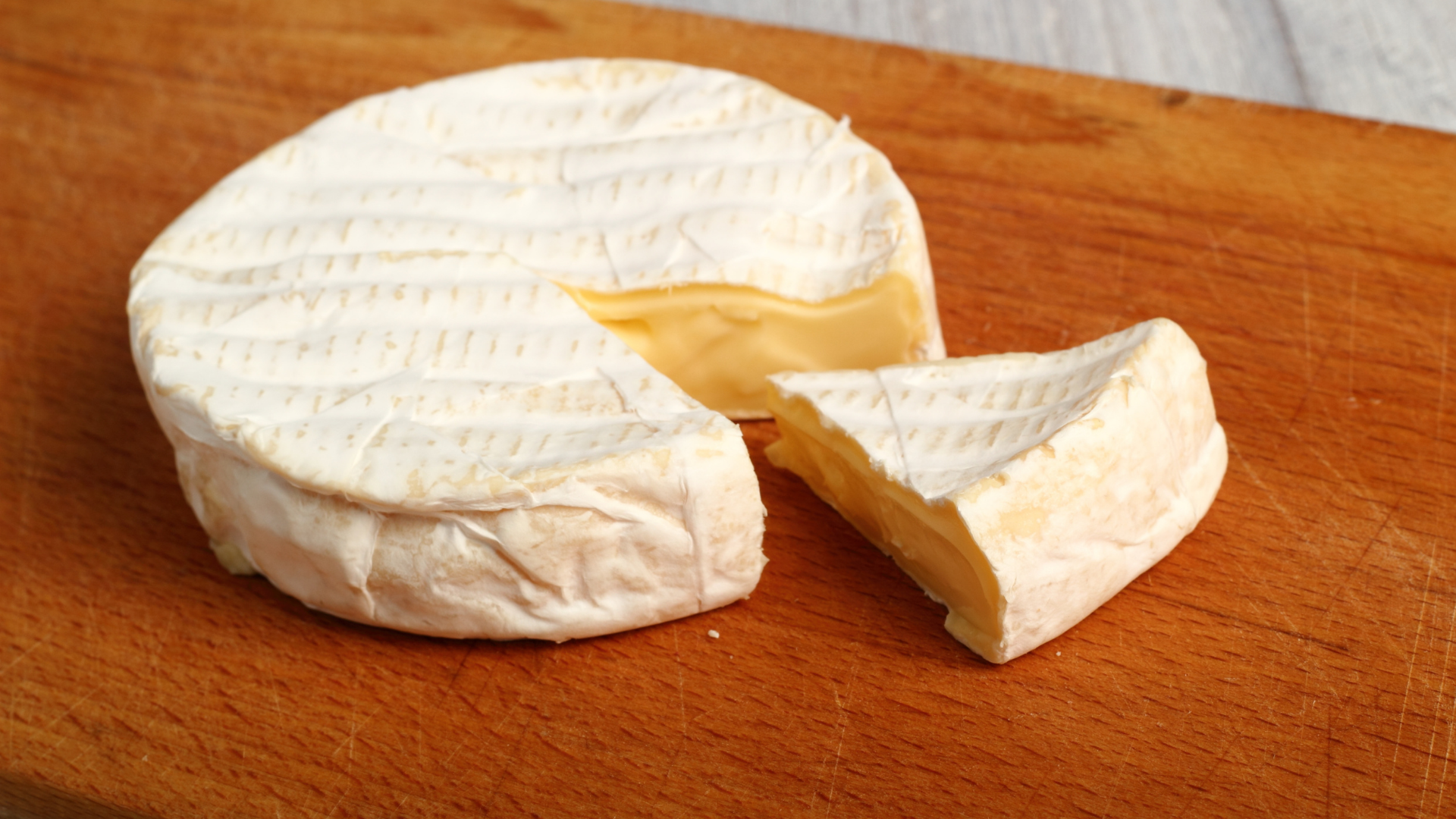 Camembert Cheese on a cutting board with a slice cut out of it.
