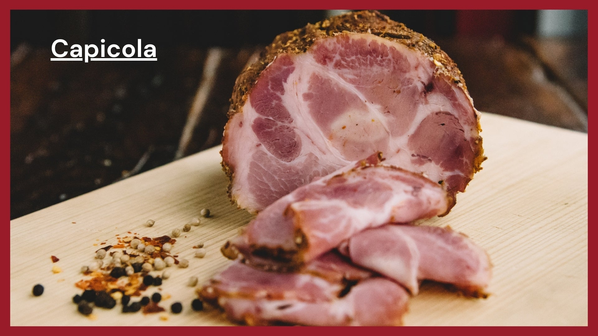 Capicola shot and cut at the mid section to show it's marbling with thing slices in the foreground.