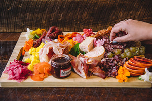A colorful charcuterie board filled with meat, cheese, vegetables, fruits and a jar of jam in the front. The charcuterie board is on a wood table and a hand grabbing a piece of meat off the board enters the image from the right.