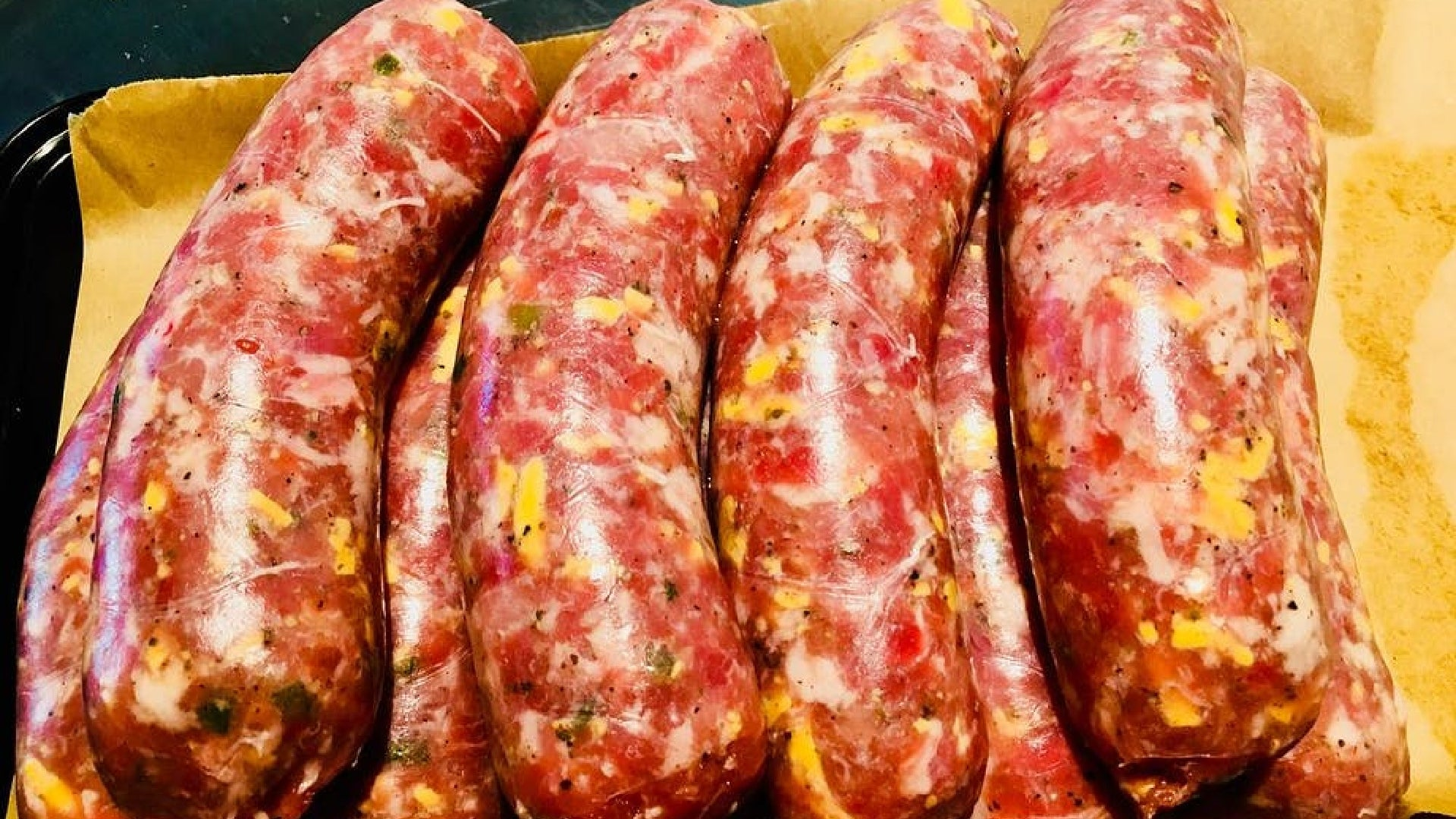 A picture looking down at several uncooked cheddar sausages stacked on top of each other on parchment paper.