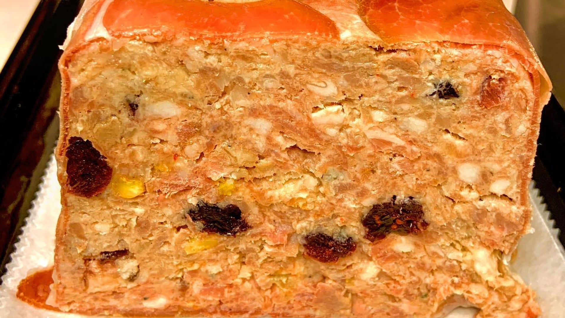 An up close picture of the cross section of country pâté to show the detail of the meat dish.