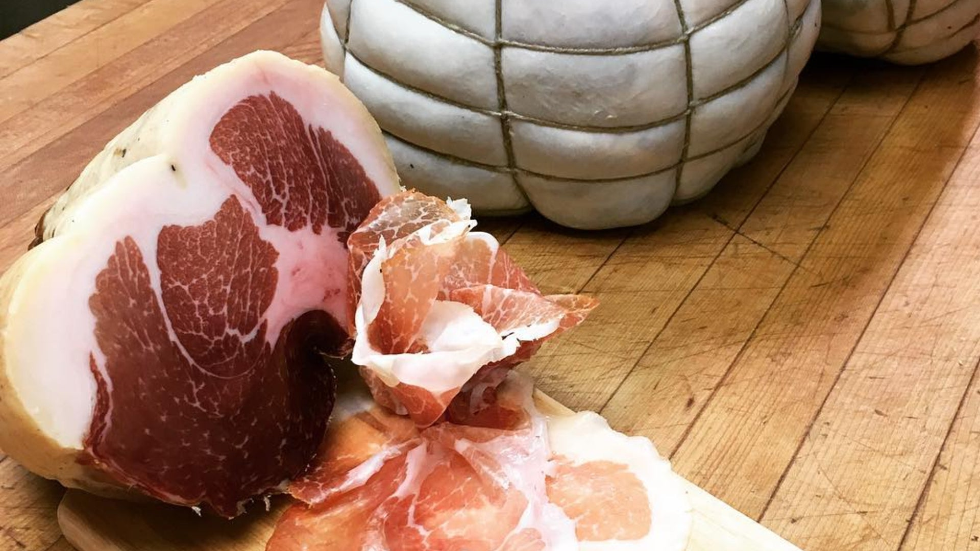 Culatello meat on a butcher table with several slices of the meat next to the whole chub.