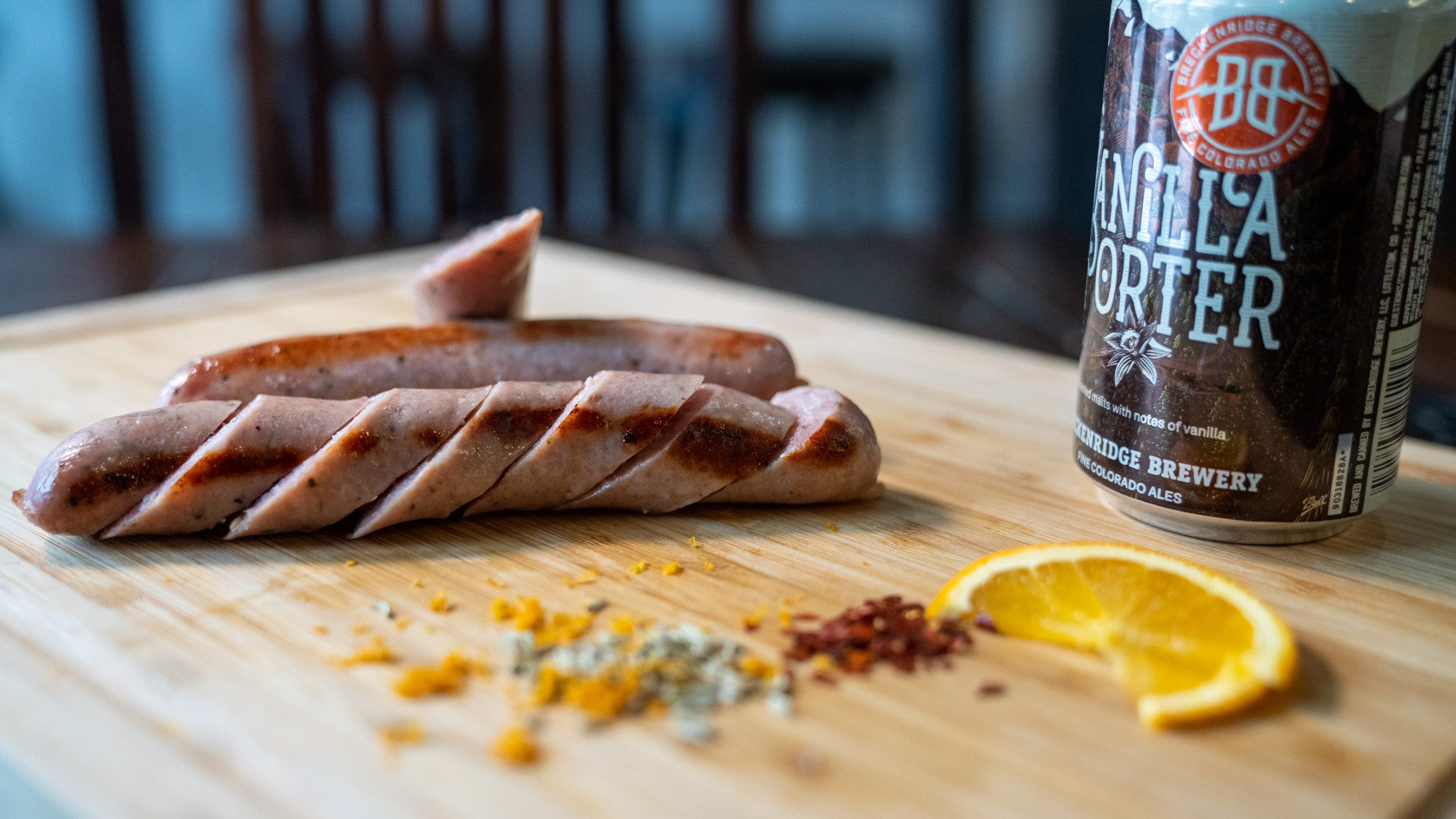 A picture of sliced sausage on a cutting board with ingredients and a Breckenridge Brewery Avalanche beer that is used to flavor the sausage.
