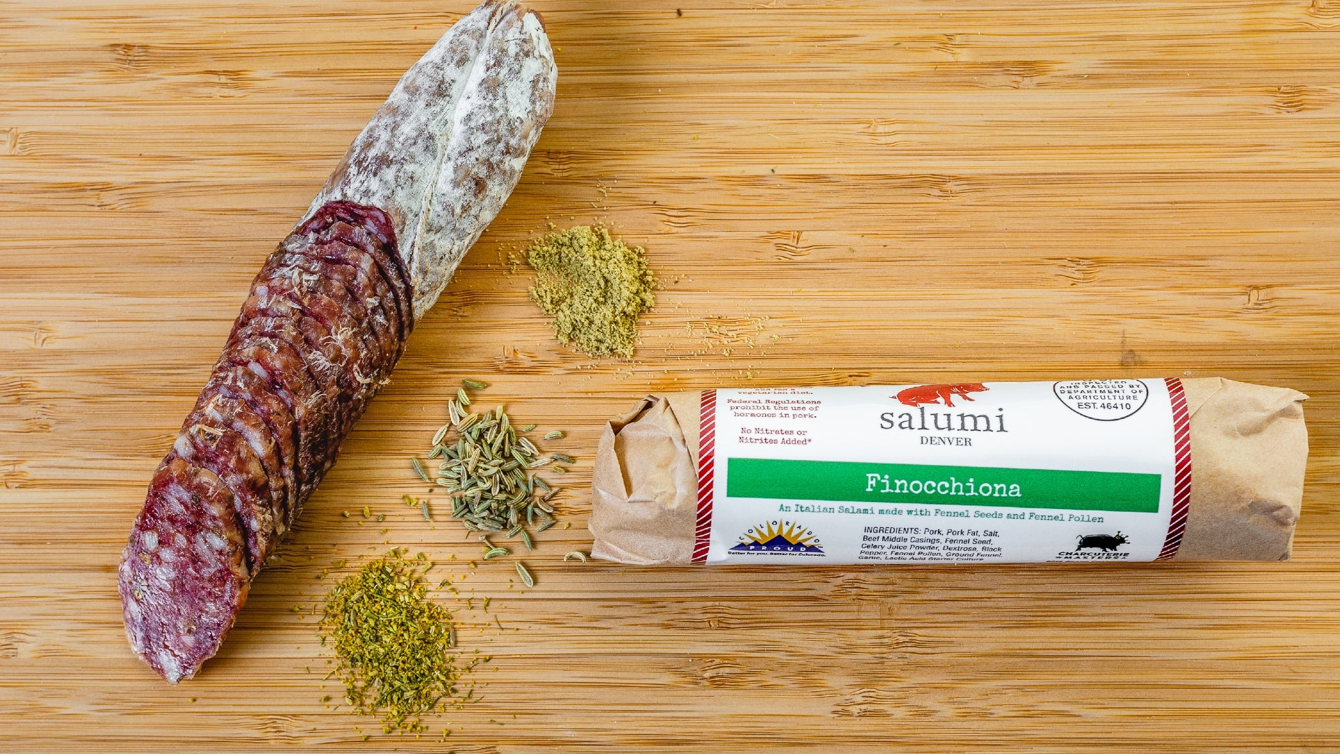 Two pieces of Finnochiana salami, one in packaging and one cut into pieces, on a cutting board with spices in between them.