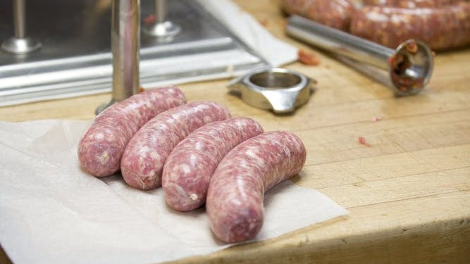 Four fresh sausages displayed on a butcher table with sausage making equipment in the background.