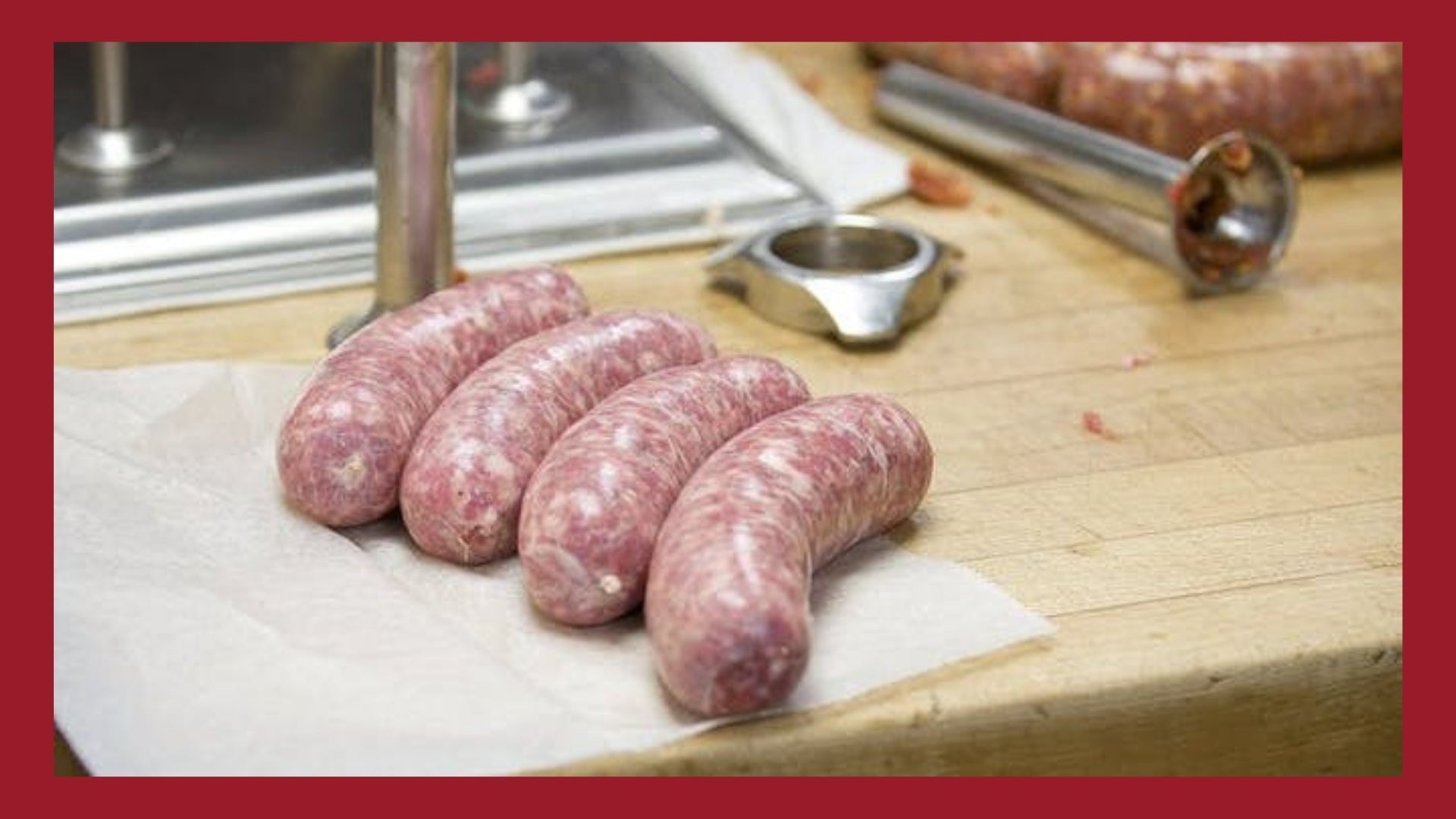 Fresh bratwursts on a butchers table with sausage stuffing equipment in the background.
