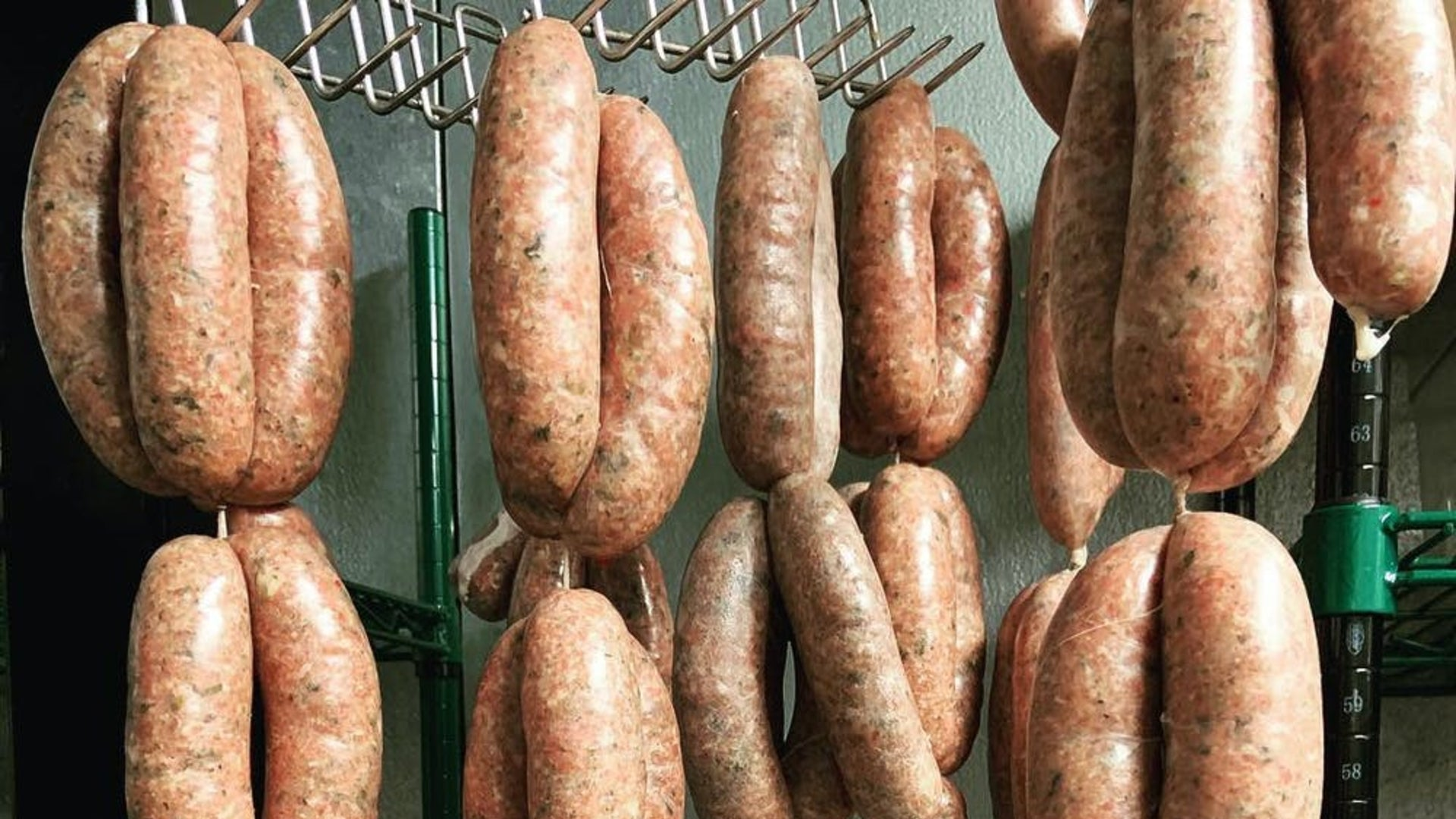 Several sets of sausage links hanging in a smoker to show the equipment needed to smoke sausages when they're hanging.