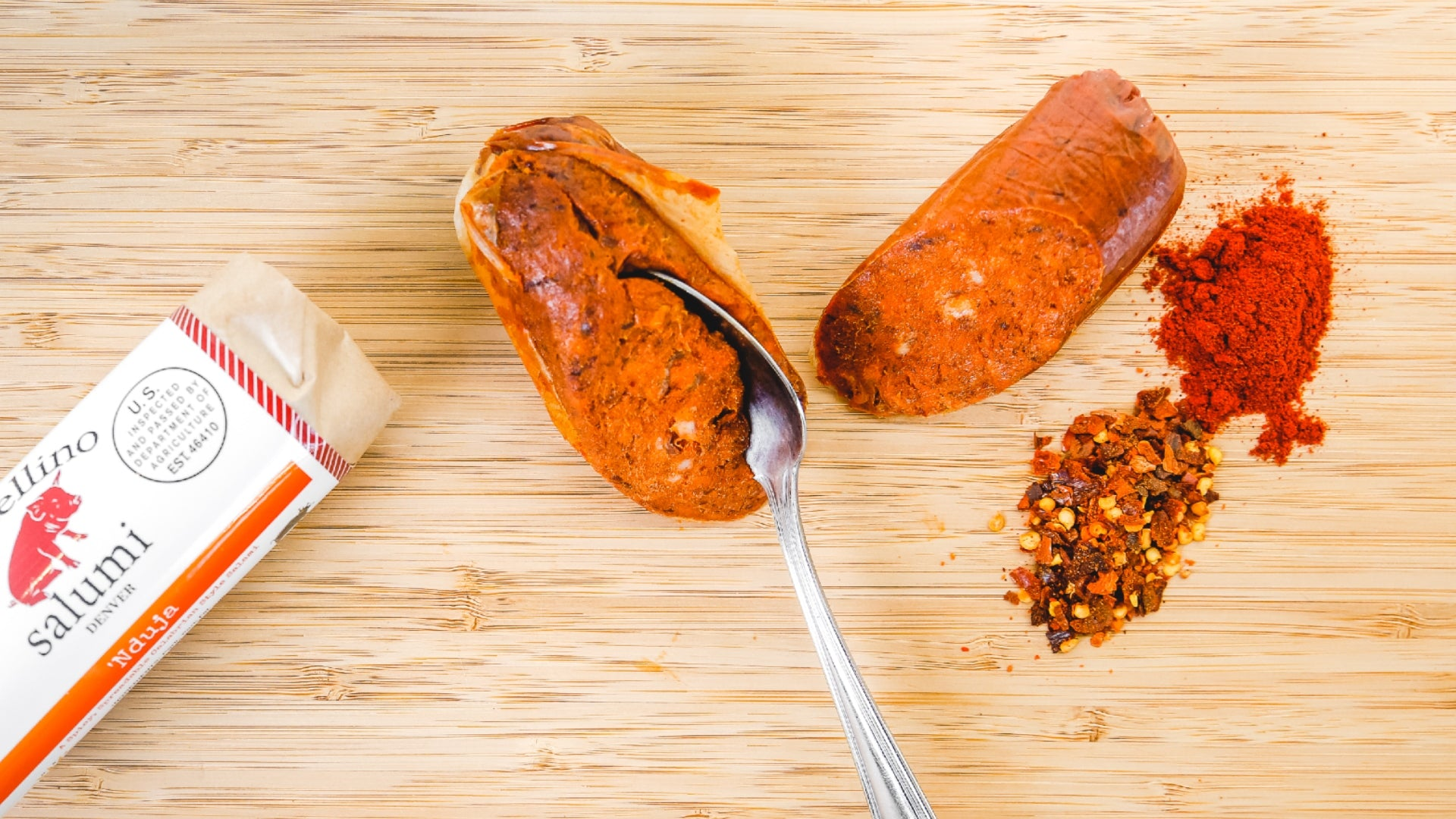 A picture shot from above of 'Nduja Salami on a cutting board. One chub of the salami is in it's packaging while the other chub has a spoon cutting into it to show that it's spreadable.