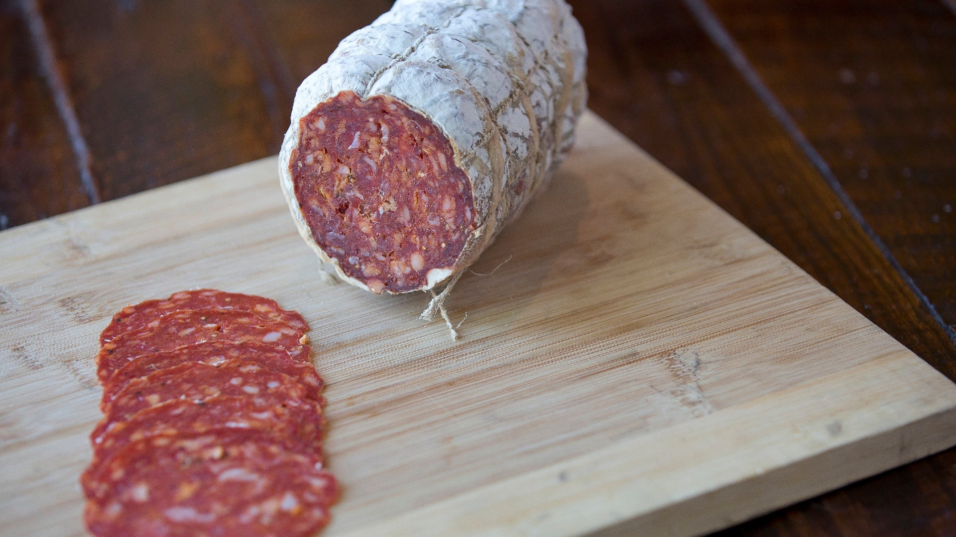 The cross section of a chub of Pepperoni salami on a cutting board with pepperoni slices in the foreground.