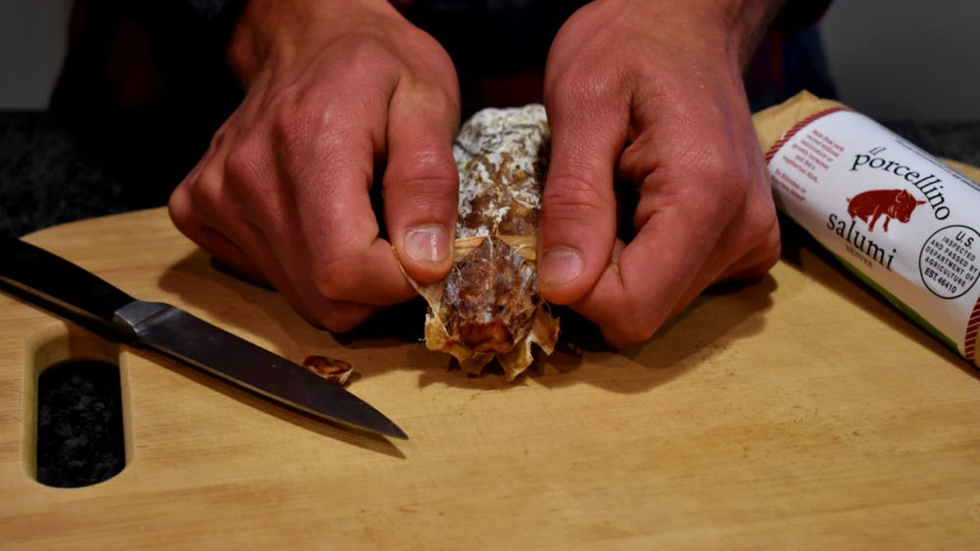 A picture showing someones hands pulling the casing off salami to show how to remove the protective mold.